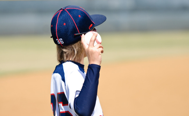 little league baseball player holding a ball